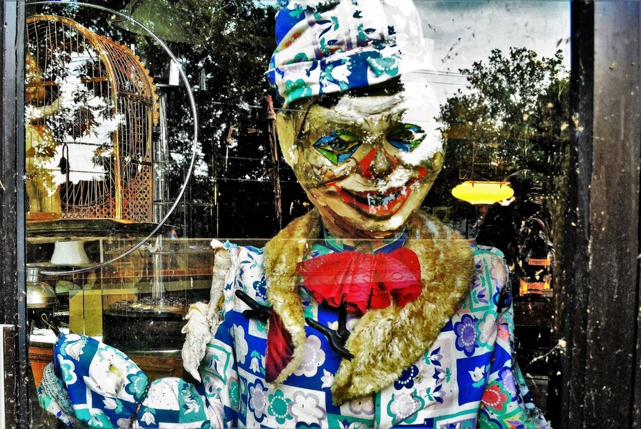 I saw this life-size clown in bad disrepair, peering out of a grimy window in the back of a store...
