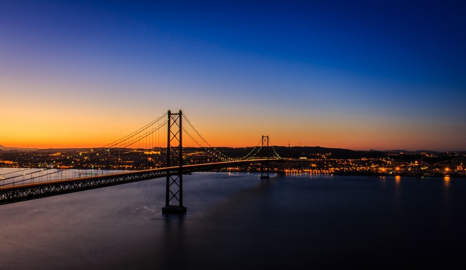 Sunset from Cristo Rei sanctuary looking over Lisbon, Tejo River, and the 25th of April Bridge. T...