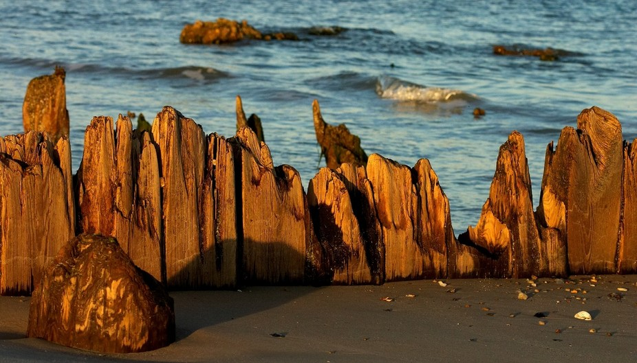 Beach with remnants of weather worn wooden wall at edge.