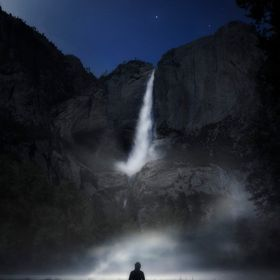 an eerie self portrait in front of Yosemite falls in Yosemite national park California on a moon lit foggy night.
