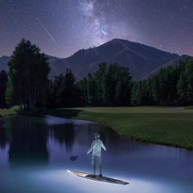 A Stand Up Paddleboarder glimpses a shooting star while enjoying the Milky Way from Sun Valley, Idaho.  To light the water, I stuffed remotely-tr...