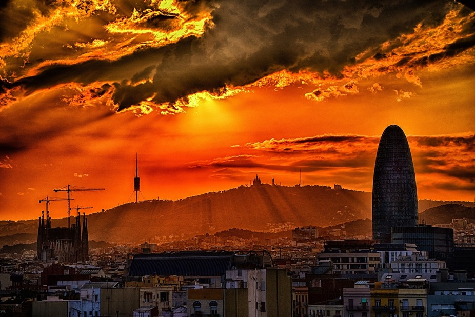 Sagrada Familia and Agbar tower In front of the mount Tibidabo while the sun is setting down in B...