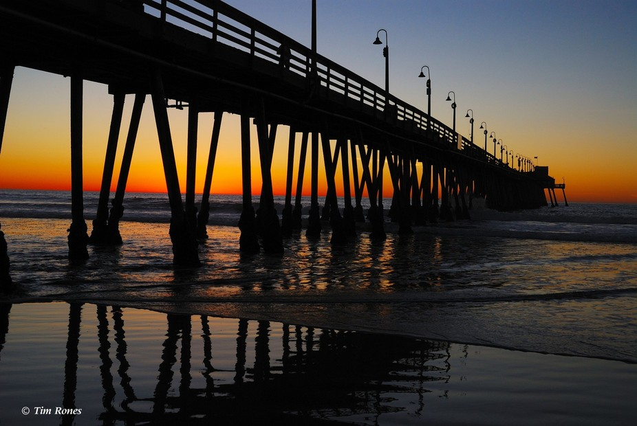 A Southern California pier just after dusk with reflections