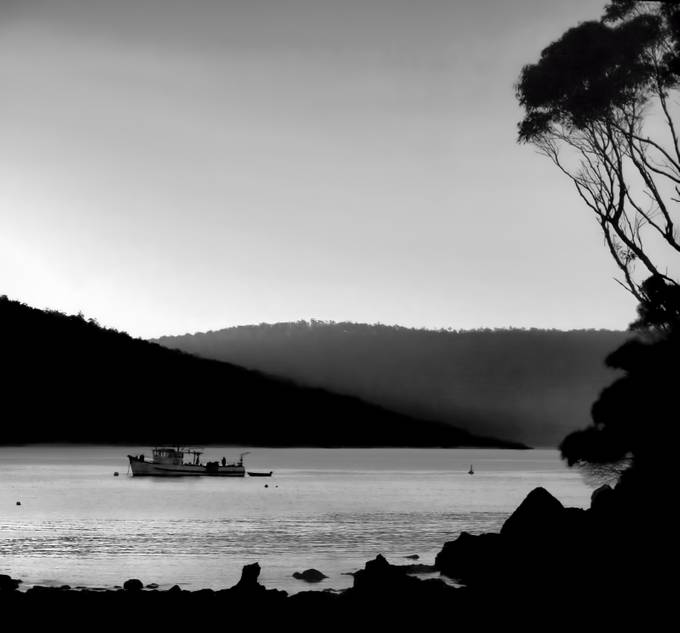 Fishing boat is moored and cool evening mist begins to settle around the hills.
