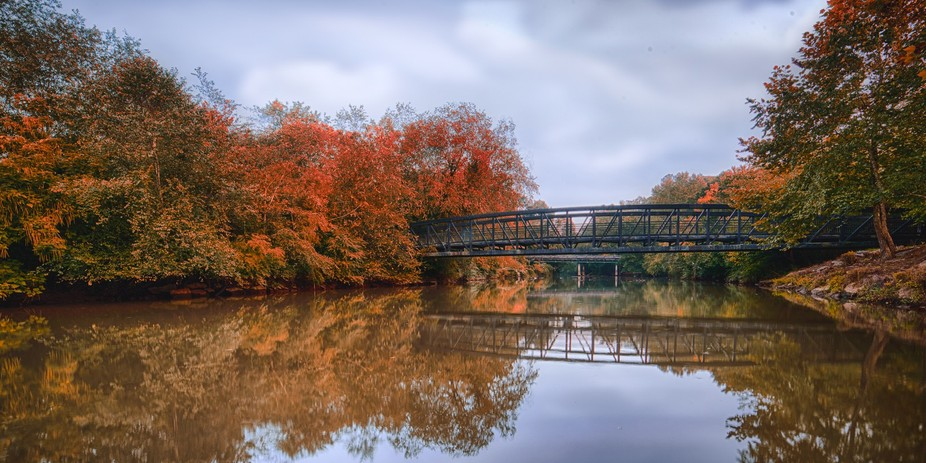 Gorgeous fall colors surround the footbridge over the Chattahoochee River at Riverside Park in Ro...