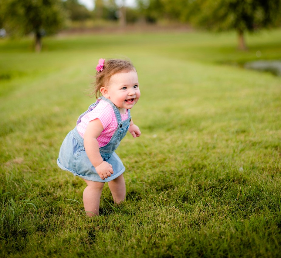 Toddler getting ready to run away from her daddy