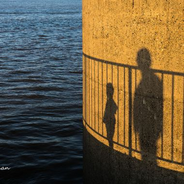 Shadows on a pier of a Father and his son