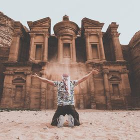 my friend euphorically celebrates the end of a long, sweaty hike to one of the beautiful temples in Jordans famous Petra