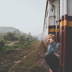 My two friends enjoy the cool morning air after a stuffy hot night along the trains north from Bangkok to Chiang Mai. The passing landscape is bl...