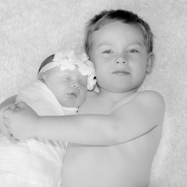 B&W of brother and sister durning a newborn photo shoot.