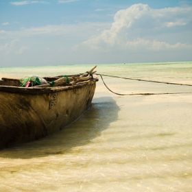 A fishing boat waits for the tide to come in on Jambiani Beach on Zanzibar