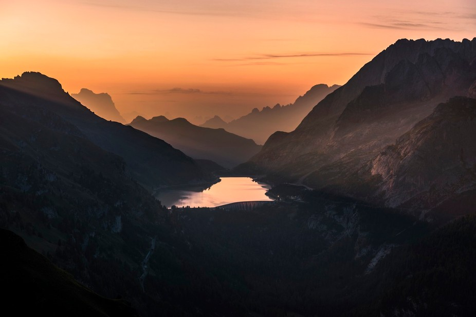 Sunrise over Lago Fedaia with views of Pelmo, Civetta and Punta Serauta on the Marmolada.