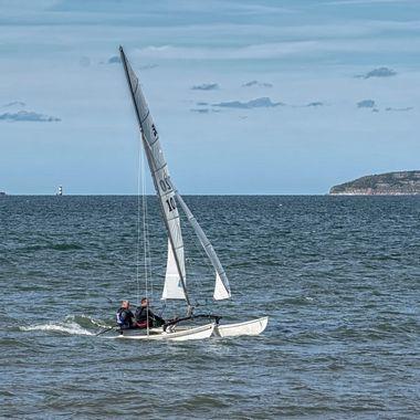 A catamaran sailing at Llanfairfechan, North Wales. A fine day for sailing.