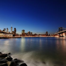 A night photo of the  Brooklyn and Manhattan bridges taken from the New Jersey shore.