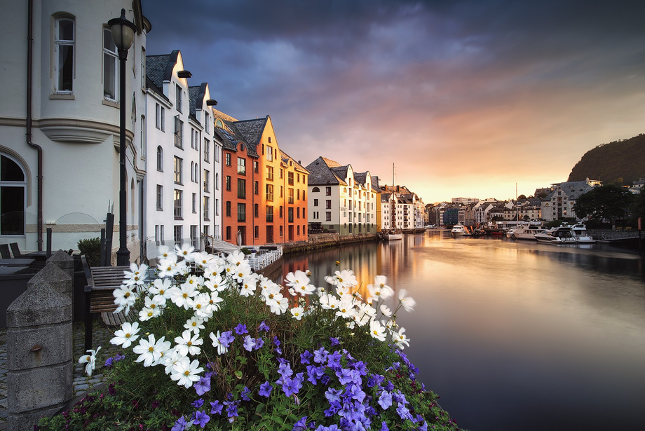 The beautiful art nouveau houses by the inner channel in Ålesund lightened by the rising sun
