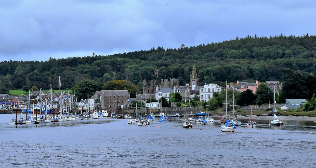 A view across the river Dee towards the old town of Kirkcudbright. This shows the old fishing harbour, with boats at anchor against the harbour wall, to the left. To the centre and right is the leisure craft marina. Set against the backdrop of trees is the spire of the towns parish church.