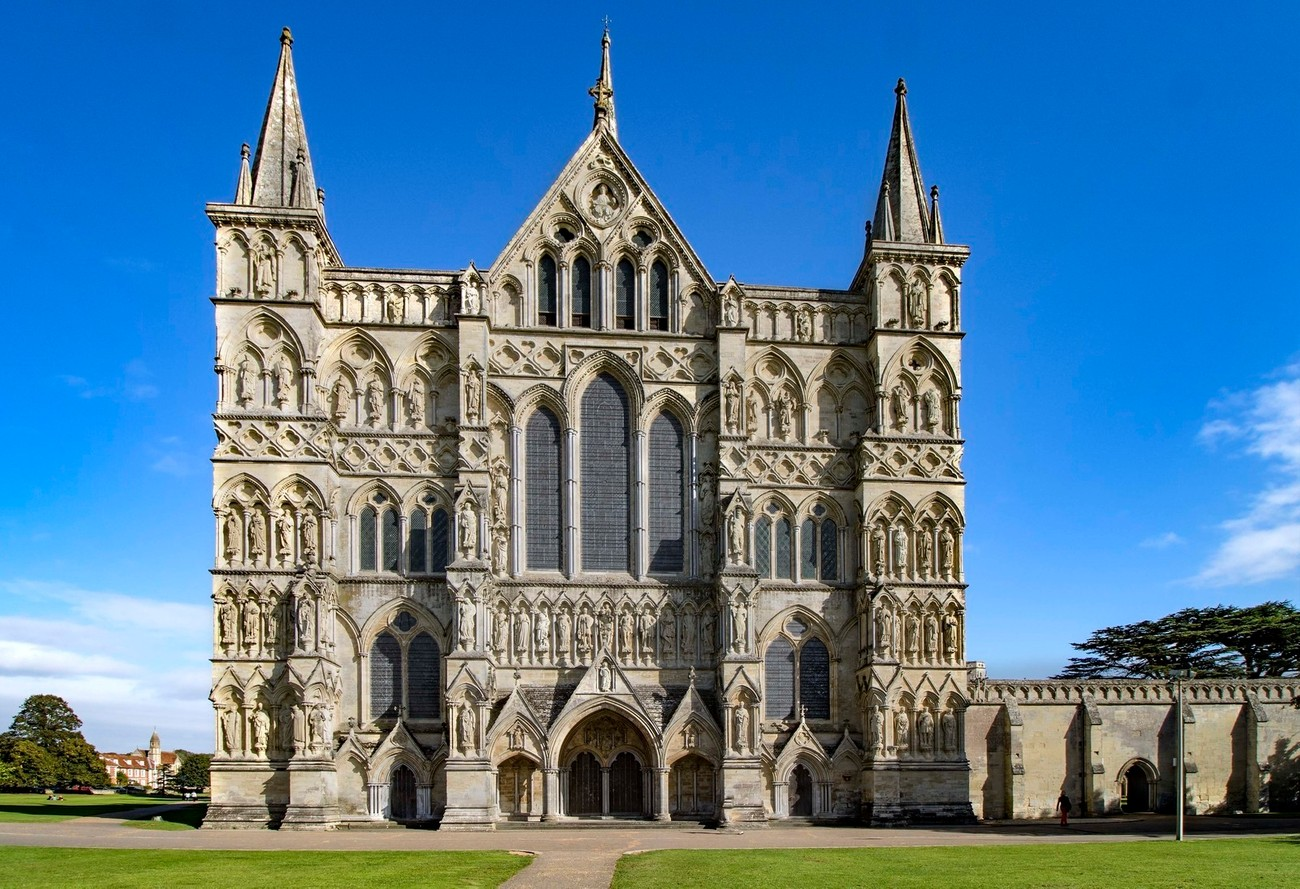 A close view of the main facade of Salisbury cathedral which dates back to the 12th century AD.  Statues covering the front of Salisbury cathedral represent important religious figures and dignitaries through the ages from the 12th century to the present day.