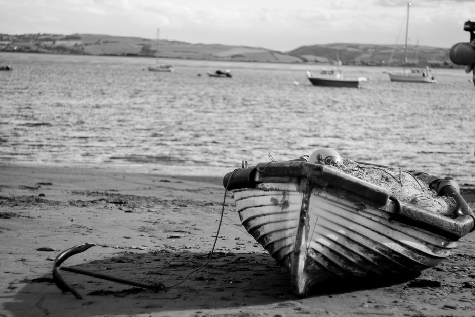 Black and white boat with anchor on the beach