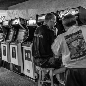 Three players in a retro arcade tournament enjoy the games at Funspot.