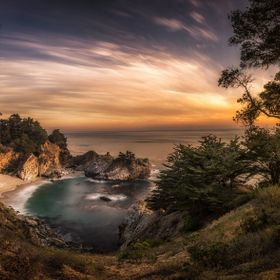 Sunset at the iconic McWay falls in Big Sur. The waterfall flowing into the Pacific Ocean