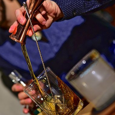Craft Bartender creating an amazing drink, Oaxaca Antigua, at the Treaty House in Fredericksburg Texas.  The foreground is a glass inverted to capture smoke off the burnt cedar plank while he creates the foundation drink to be poured over an ice sphere.