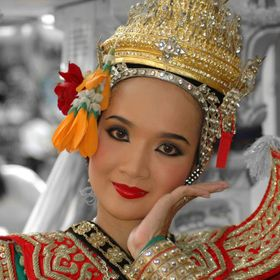 This Thai classical dancer had just finished putting on her costume and was preparing to perform at a busy tourist-packed street in Bangkok. As s...