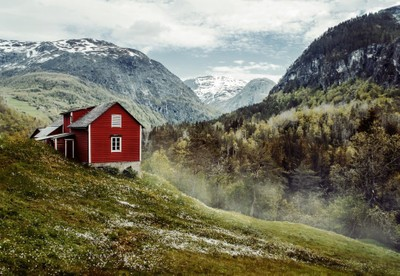 Red wooden cottage in the valley