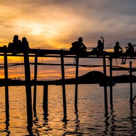 A couple spending their own time together with each other and a group of friends enjoying the their moment with beautiful sunset at the jetty