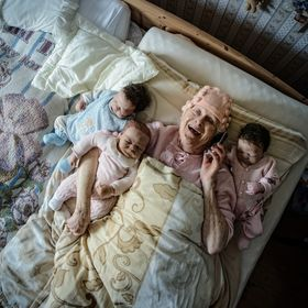Old woman is lying with three baby dolls in bed and talking on the phone with a laugh