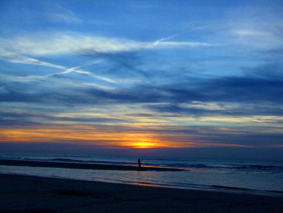 I was at the beach and there was a man fishing. The sunset was very creative that day!