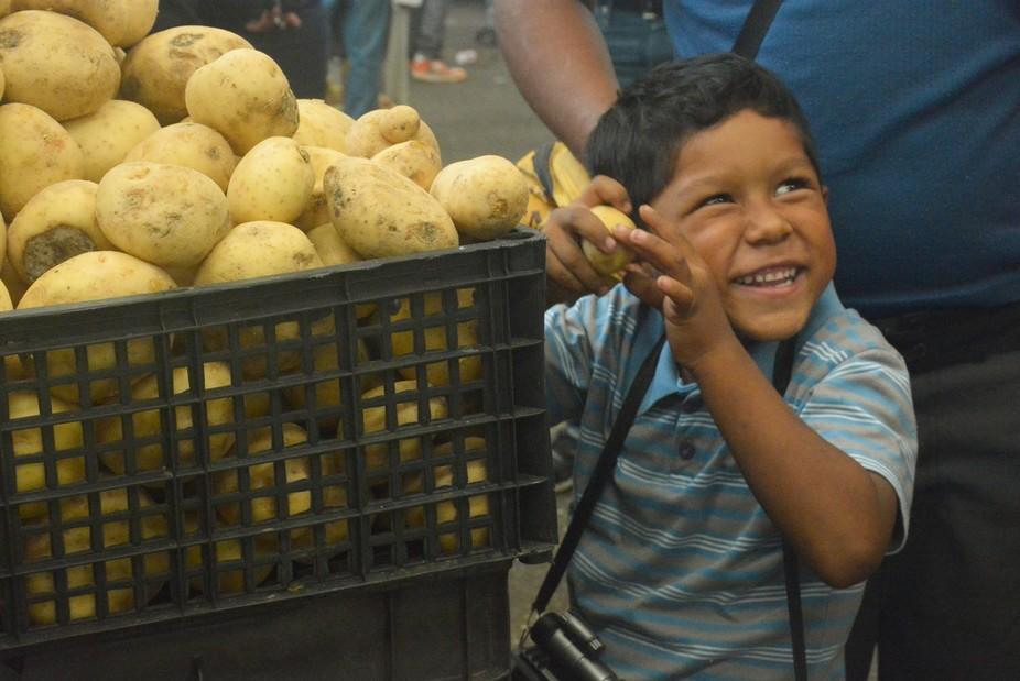Este niño se puso muy alegre en cuanto vio las papas frente a él, tomó una que observaba deten...