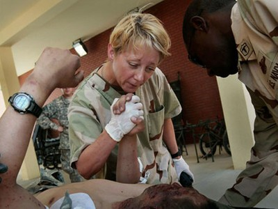 Medical staff consoles a severely wounded soldier at Kandahar Role III Hospital