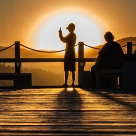 As I was setting up to get a photo of the boardwalk in Coeur d'alene with the sunset a boy and his mother walked into the shot.  They had no...