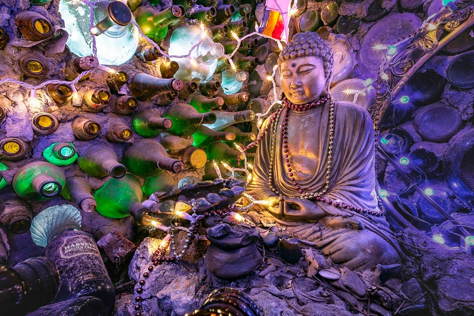 Buddha shrine setting inside a small dark niche made of empty bottles.  Tinkertown Museum, Sandia...