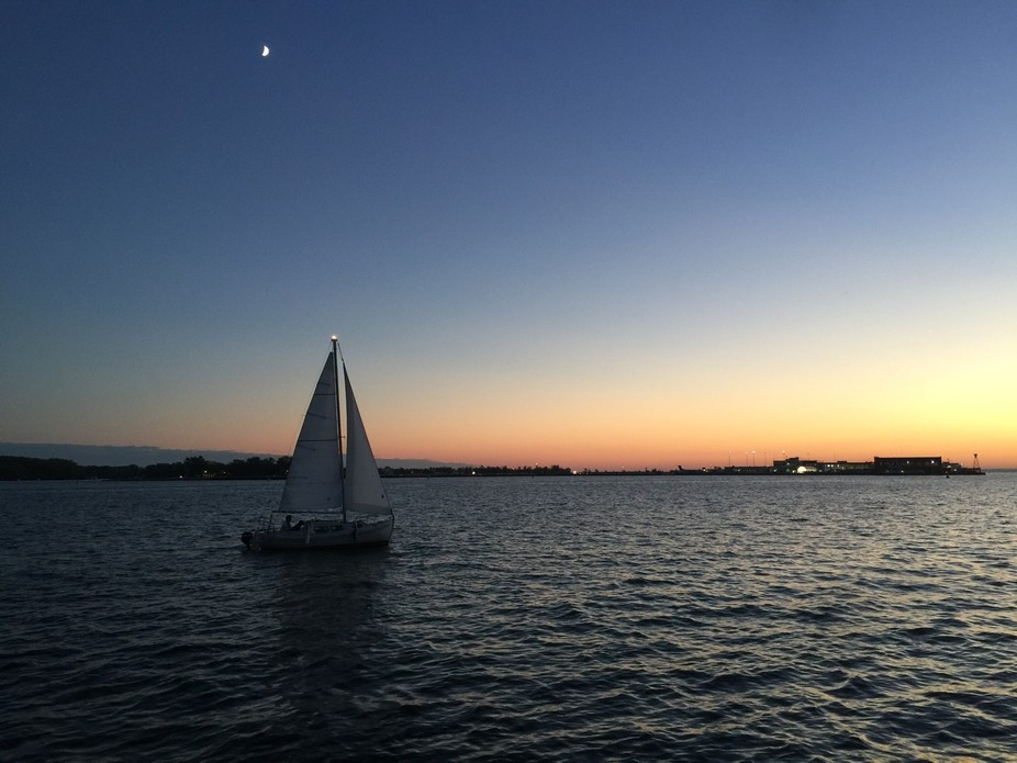 Caught this boat sailing in after sunset and it seem to light up the moon above it.