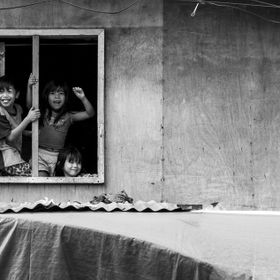 Kids waving from a window in Cebu City, Philippines