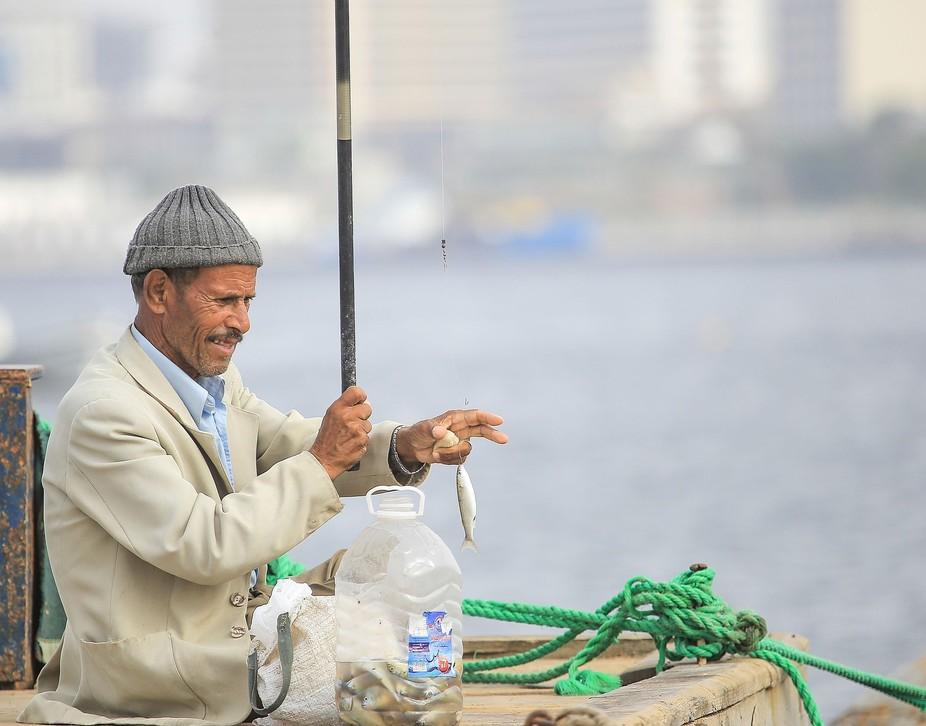 صياد السمك وهو يصطاد سمكة من على مرساة سفن
