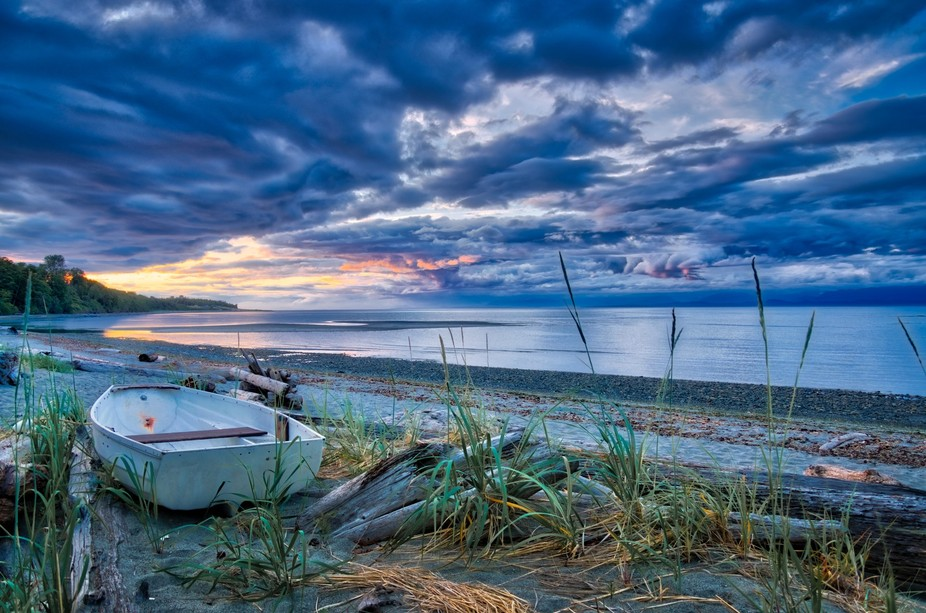 An abandoned boat sits on a beach at Kye Bay, near Comox on Vancouver Island, BC.  NOTE: This is ...