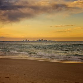 Somebody has drawn a flower on the sand at Coolangatta, Queensland, Australia. The skyline of the city of Gold Coast is seen in the distance.  | ...