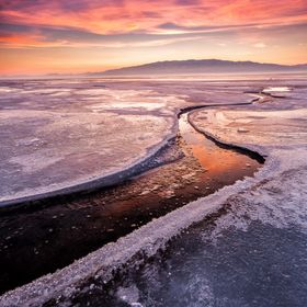 A crack in the ice on Utah Lake at sunset