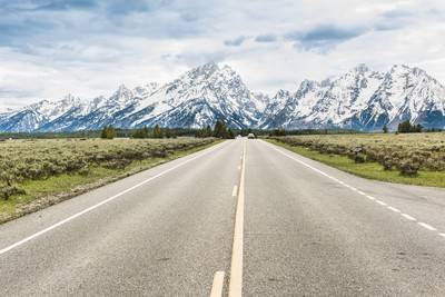 Road with cars leading to Grand Teton mountains
