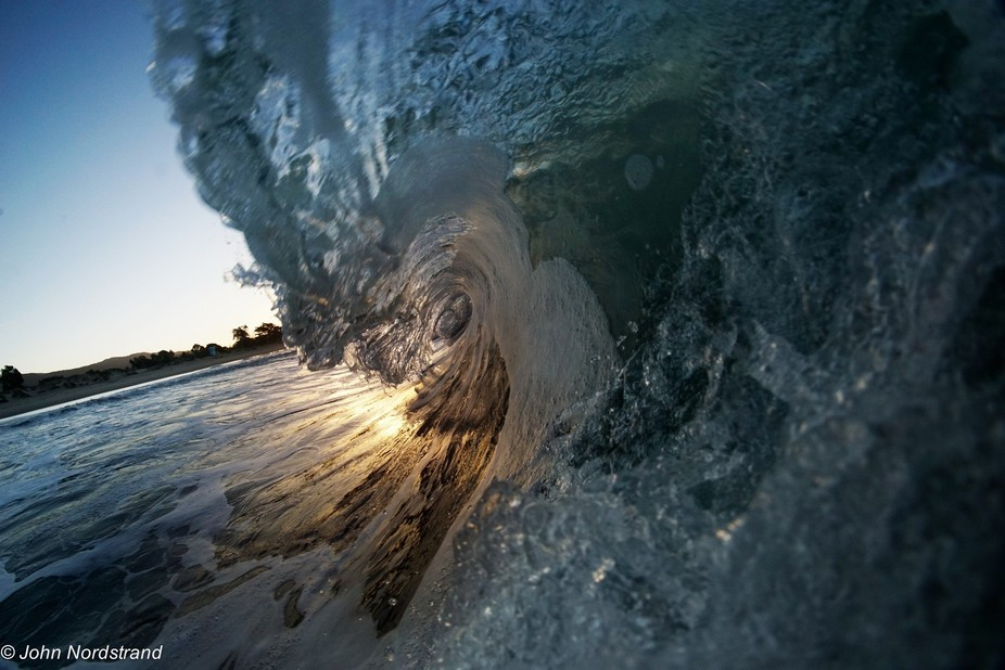 Sunrise through the barrel of a wave