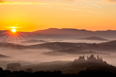 Fog, mist and the sunrise near San Quirico d'Orcia, Tuscany, Italy