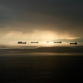 English Bay, Vancouver, British Columbia Canada. A big port, these big transports, tankers and shipping containers wait out a storm.