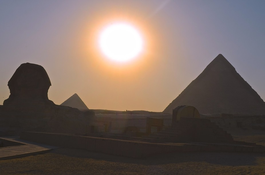The Egyptian Sphynix with the smaller pyramids in the background at sunset.
