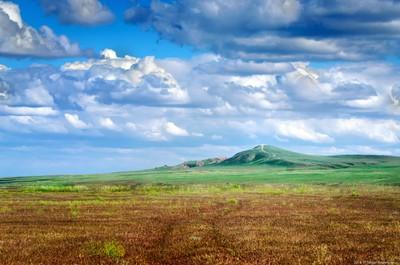 Bogdo mountain under beautiful sky. Panorama of steppe near salt lake Baskunchak