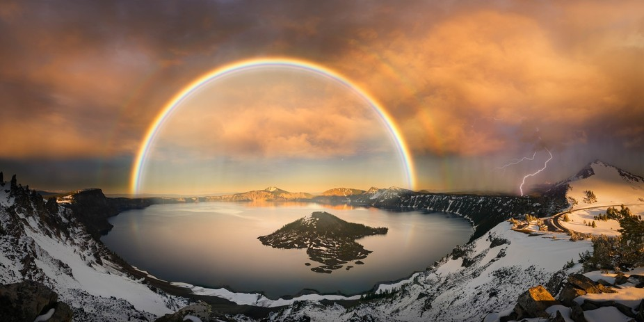 The panoramic view of Crater Lake with rainbow and lightning at sunset hour.  Warning: Some locat...