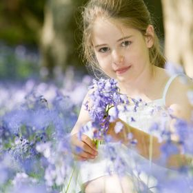 Portrait of a little girl collecting wild flowers in a bluebell wood