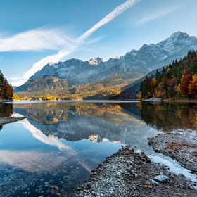 Another colourful and calm day at the lake Eibsee with Zugspitze on background.