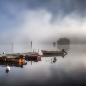 Mist ascending from a perfect calm Lake with small boats